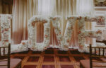 Large floral love sign in Victoria & Albert Ballroom wedding venue at the Prince of Wales Hotel in Niagara-on-the-Lake
