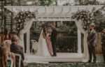 Couple saying their vows at the Courtyard Rose Garden wedding venue at the Pillar & Post in Niagara-on-the-Lake