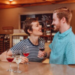 Couple laughs as they enjoy a glass of wine each in a wine tasting room