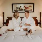 couple in bed in the main mill guestroom at millcroft inn and spa