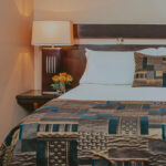 Queen size beds with stylish linens at Jordan House in Jordan Village