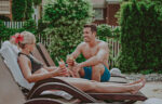 Couple relaxing on lounge chairs at the Poolside Patio at the Pillar & Post Hotel in Niagara-on-the-Lake